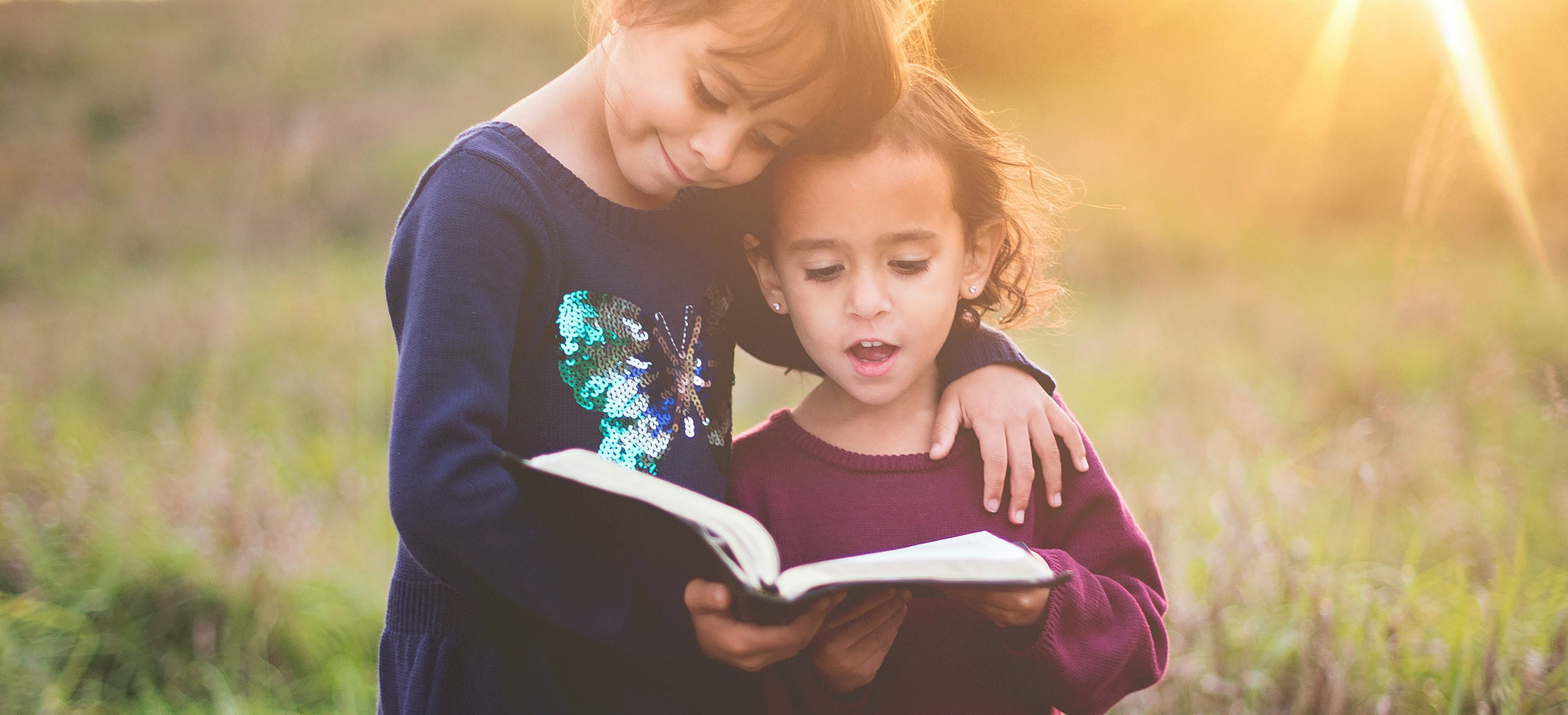 two young children holding a bible, reading and smiling outside