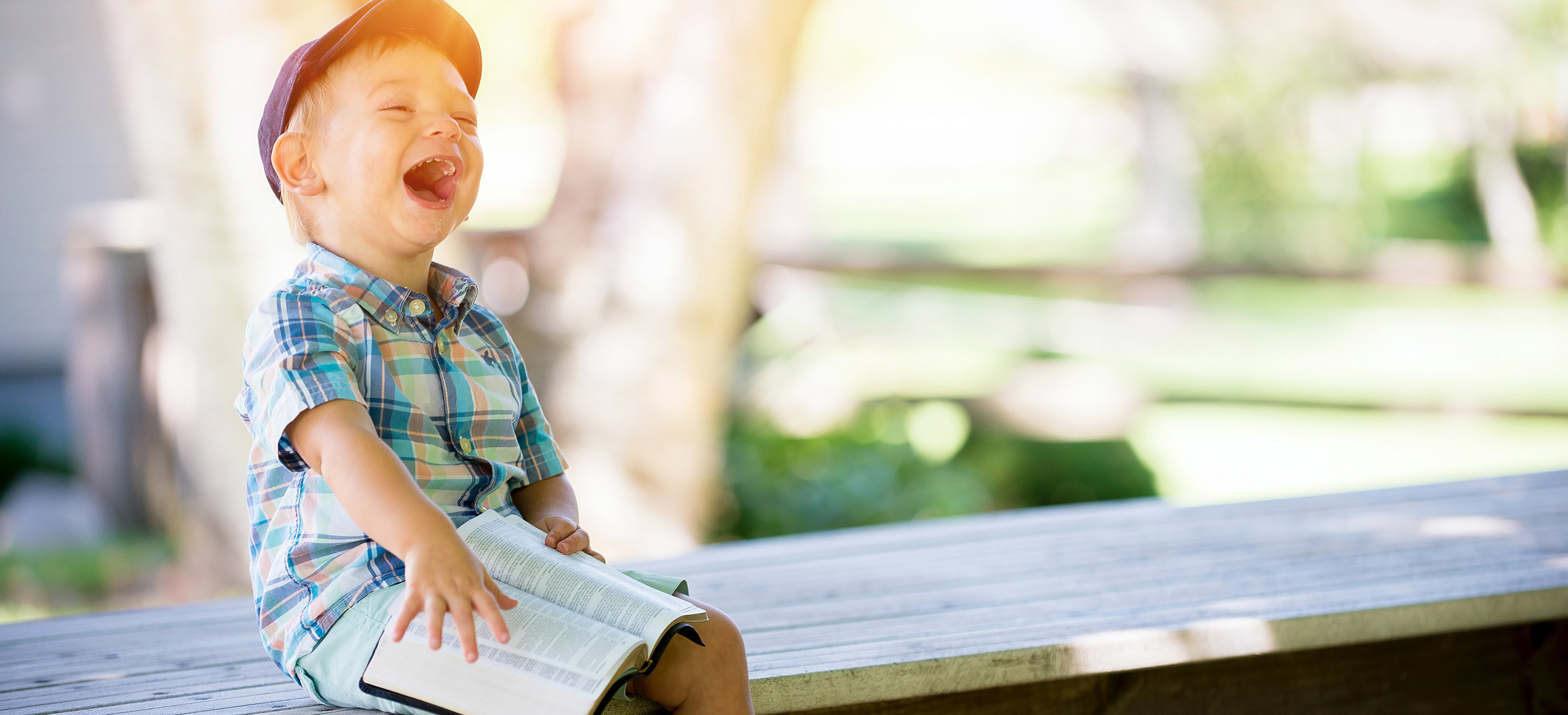 Toddler boy with bible sitting on park bench